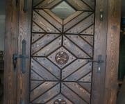 sosnowe drzwi wejściowe z rozetami i okienkiem